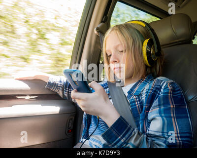 Boy using mobile phone while listening music in car - Stock Photo