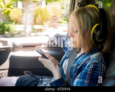 Boy looking at mobile phone while listening music in car - Stock Photo