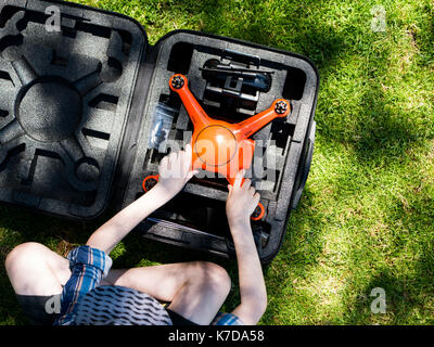 Overhead view of boy removing quadcopter from container while sitting on grassy field at playground - Stock Photo