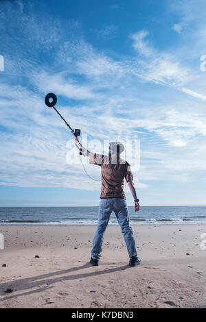 Rear view of man holding recreational metal detector at Horsey Beach - Stock Photo