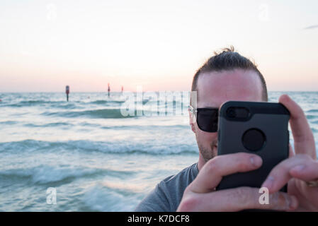Man photographing through smart phone against seascape during sunset - Stock Photo
