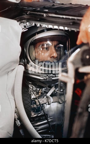 Astronaut Alan B. Shepard in his space suit and helmet inside the Mecury capsule where he is undergoing a flight - Stock Photo