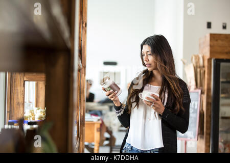 Woman reading label on jar while holding coffee cup in cafeteria - Stock Photo