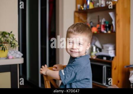 Portrait of happy boy looking over shoulder at home - Stock Photo