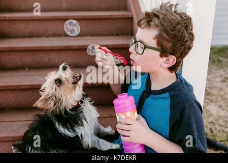 Boy playing with bubble wand while sitting by dog on steps - Stock Photo