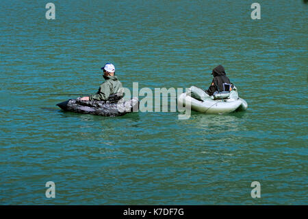 Two fishermen in float-tubes on a lake in Provence - Stock Photo