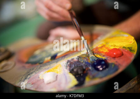 Close-up of man with watercolor paint palette in workshop - Stock Photo