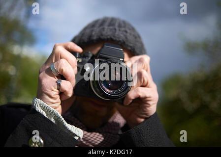 Close-up of man photographing through DSLR camera in Paris - Stock Photo