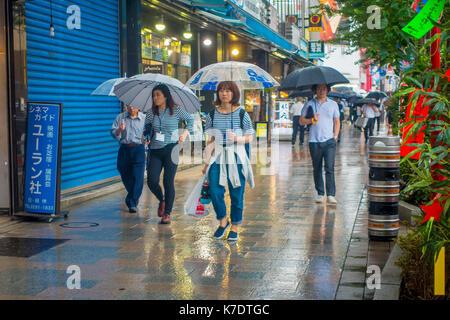 TOKYO, JAPAN JUNE 28 - 2017: Unidentified people walking under the rain in the sidewalk with umbrellas in Jimbocho - Stock Photo