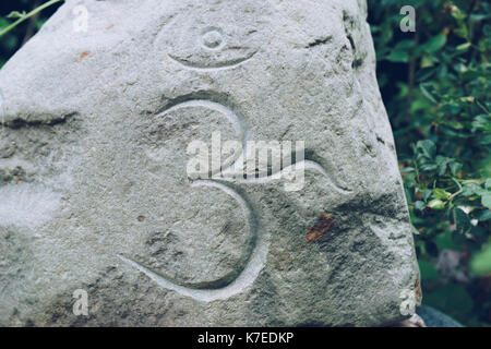 Om Symbol writtng on a big stone - Stock Photo