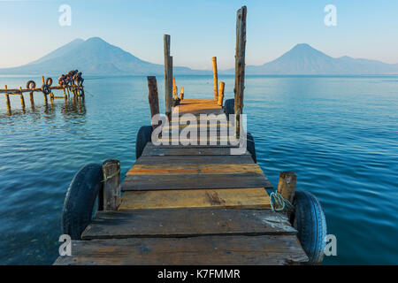 Young boys fishing on a pier by the Atitlan Lake at sunrise with volcano San Pedro in the background near Panajachel - Stock Photo