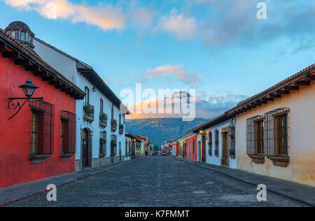 A colorful street at sunrise in the historic city center of Antigua with the Agua volcano in the background, Guatemala, - Stock Photo