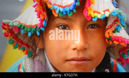 Portrait of a young indigenous girl of the Uros tribe living on the Titicaca Lake near the city of Puno, Peru. - Stock Photo
