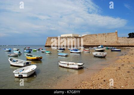 View of the castle with fishing boats in the foreground, Cadiz, Cadiz Province, Andalusia, Spain, Western Europe. - Stock Photo