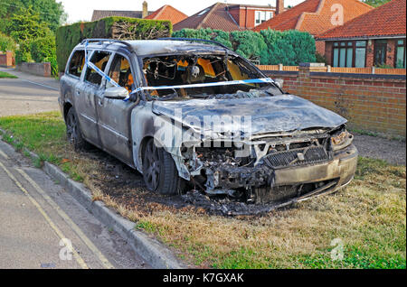 A burnt out car with Police tape on the roadside at Hellesdon, Norfolk, England, United Kingdom. - Stock Photo