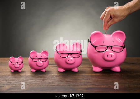 Close-up Of Person Hand Inserting Coin In Pink Piggybank On Table - Stock Photo
