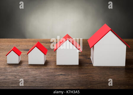 Different Size Houses In Row On Wooden Table - Stock Photo
