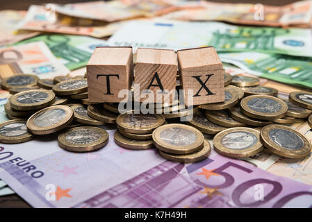 Close-up Of A Wooden Blocks With Word Tax On Euro Currency - Stock Photo