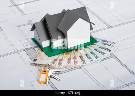 Close up of house model with banknotes and keys on blueprint stock close up of house model with banknotes and keys on blueprint stock photo malvernweather Images