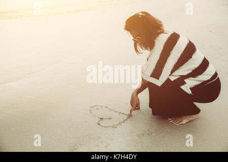 Single broken heart girl concept. Hipster alone women drawing one heart with her finger on the sea beach vintage - Stock Photo