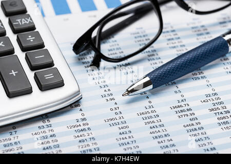 Close-up Of A Calculator With Pen And Eyeglasses On Data Sheet - Stock Photo