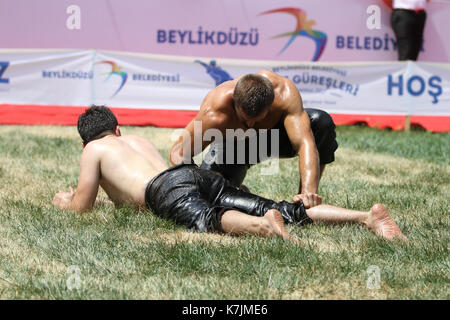 ISTANBUL, TURKEY - JULY 30, 2017: Oil wrestlers compete in Beylikduzu oil wrestling festival. Oil wrestling also - Stock Photo
