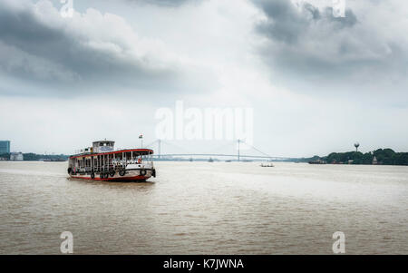 Public ferry crosses Hooghly river on overcast monsoon morning with view of new Howrah bridge in background in Kolkata, - Stock Photo