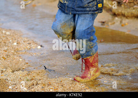 A child or kid wearing red wellies wellington boots and covered in mud and water wet through jumping in puddles - Stock Photo