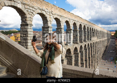 Tourist taking selfie photographs with smartphone on selfie stick at famous spectacular Roman aqueduct, Segovia, - Stock Photo