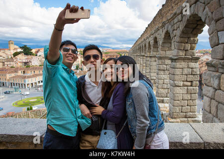 Young Chinese tourists taking selfie photographs with iPhone smartphone at famous Roman aqueduct, Segovia, Spain - Stock Photo