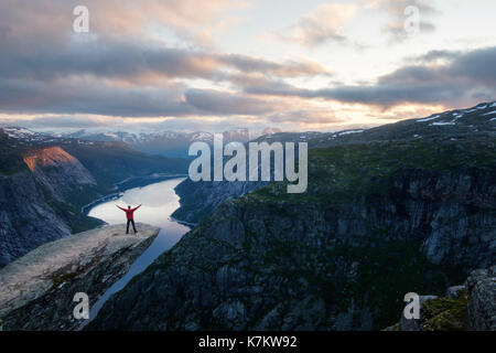Alone tourist on Trolltunga rock - most spectacular and famous scenic cliff in Norway - Stock Photo