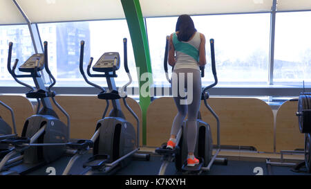 Young fit woman using an elliptic trainer in a fitness center and smiling. girl on Elliptical trainer. young woman - Stock Photo