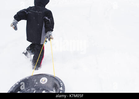 Young boy pulling a sled up a snow covered hill in the winter. - Stock Photo