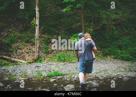 A father carries his daughter during a hike in the woods. - Stock Photo