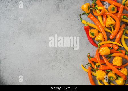 Orange and yellow peppers on stone slate - Stock Photo