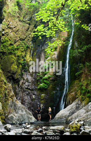 Couple at base of Niagara Falls - Goldstream Provincial Park - Victoria, Vancouver Island, British Columbia, Canada - Stock Photo