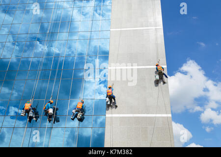 Workers cleaning windows mirror service on high rise building - Stock Photo