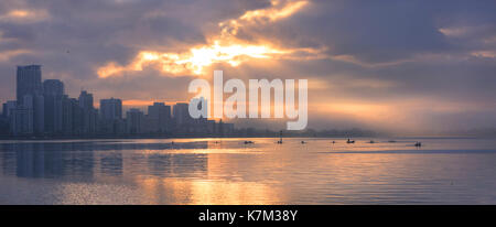 A university rowing club on the Swan River at sunrise. - Stock Photo