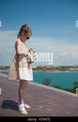 trendy little girl wearing dress and sunglasses looking for something in her pouch on sky and sea background - Stock Photo