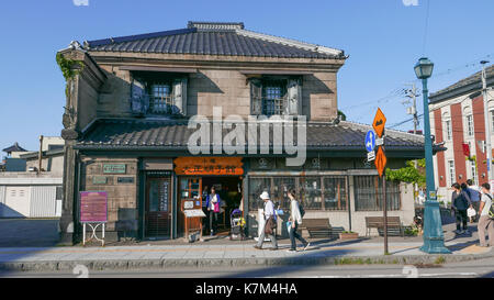 Shoppers walking past traditional storefront in Otaru Japan. Historic stone building with tourist information sign - Stock Photo