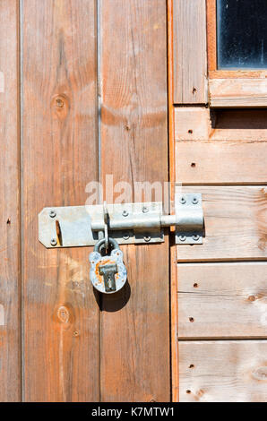 Large metal bolt and padlock on a wooden shed door - Stock Photo