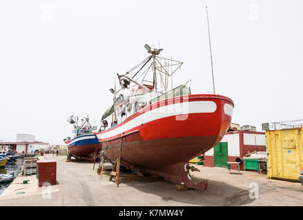 A large red boat in the dry dock at the Marina at Puerto Mogan on Gran Canaria, Spain - Stock Photo