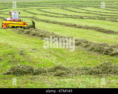 Engelberg, Switzerland - 3 August 2017: farmer on his tractor that moves the grass to make it dry at Engelberg on - Stock Photo