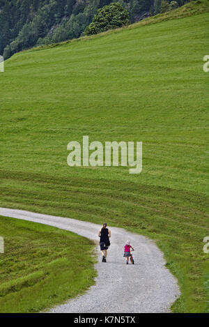 Woman and little girl with strider bike and helmet from behind walking along a gravel track in a green field - Stock Photo