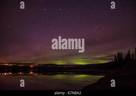 Aurora borealis lights dancing over village and lake - Stock Photo