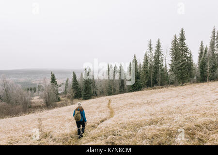 Young woman hiking on path through open field in frosty landscape - Stock Photo
