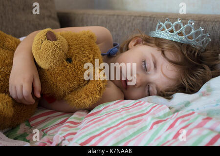 Close-up portrait little girl sleeping in bed. girl with a crown of princess on her head in bed hugging a teddy - Stock Photo