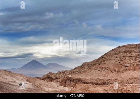 Three people in the Valle de la Luna, Chile. In the background, the peak of the Licancabur volcano. - Stock Photo