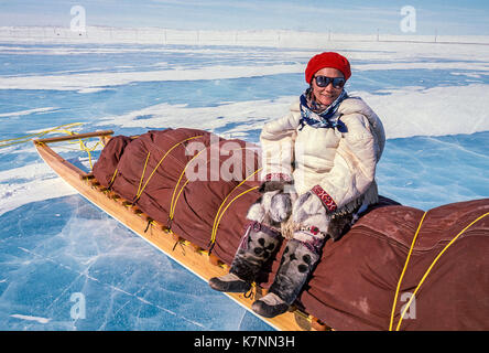 Local Inuit woman elder, dressed in traditional caribou skin clothing, sitting on a traditional Inuit cargo sled, - Stock Photo