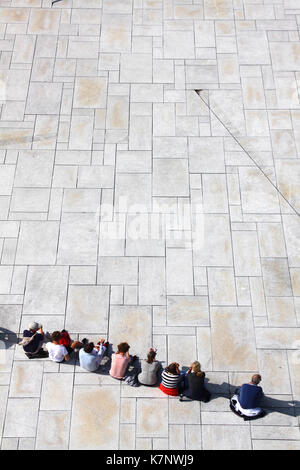 Visitors relax on the paved marble and  granite plaza in front of Oslo Opera House, Norway - Stock Photo
